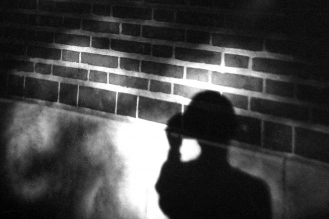student walking at night with shadow on brick wall