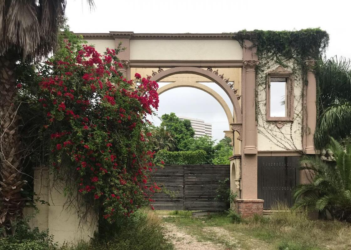 Overgrown arch with office building in background