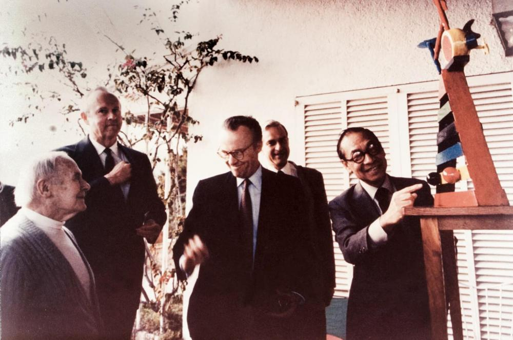 "Joan Miró, Mr. Hines, I.M. Pei, and colleagues in Miró's studio in Spain. The group was viewing the maquette of ""Personage and Birds."" The sculpture still stands outside JPMorgan Chase Tower in Houston. Courtesy Hines."